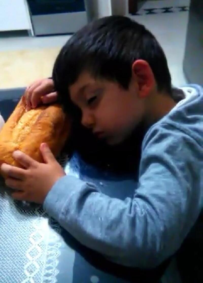 Sofrada ekmekle uyuklayan çocuk, ilgi odağı oldu